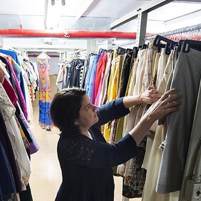 A collection manger browses costumes on a clothing rack.