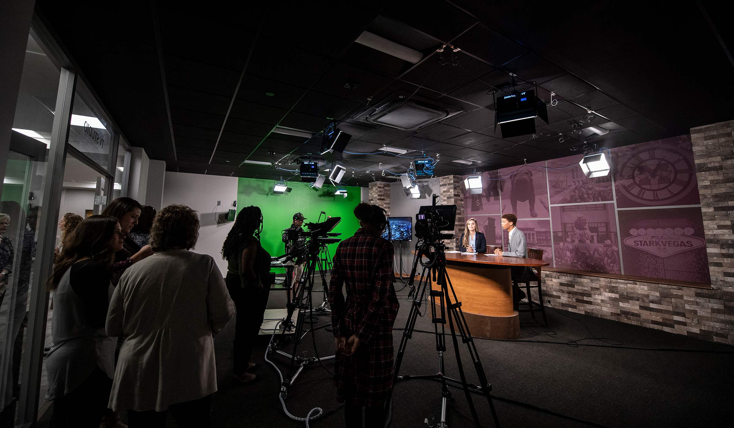 A production crew in a television studio work with students at the anchor desk.