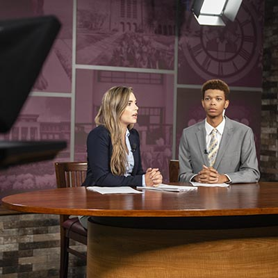 Students at the anchor desk in the TV Studio.