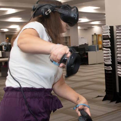 A student wears a VR headset and uses hand controllers.